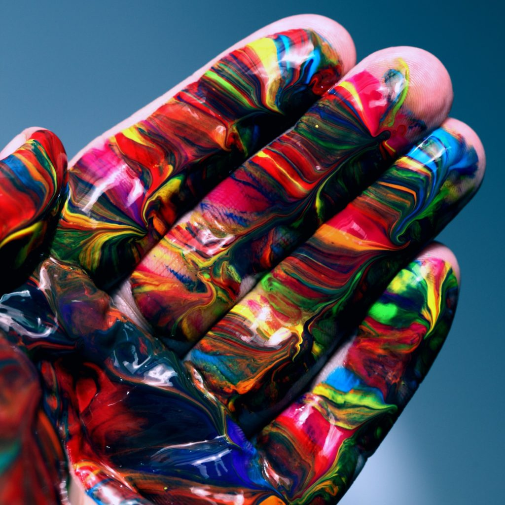 An open hand covered in multi-coloured paint
